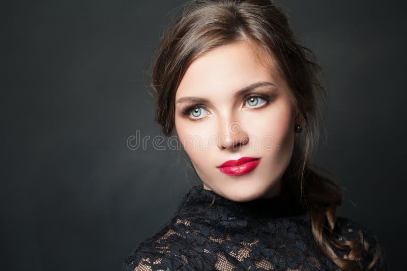 Femme élégante avec les cheveux rouges de maquillage de lèvres sur le fond foncé photo libre de droits