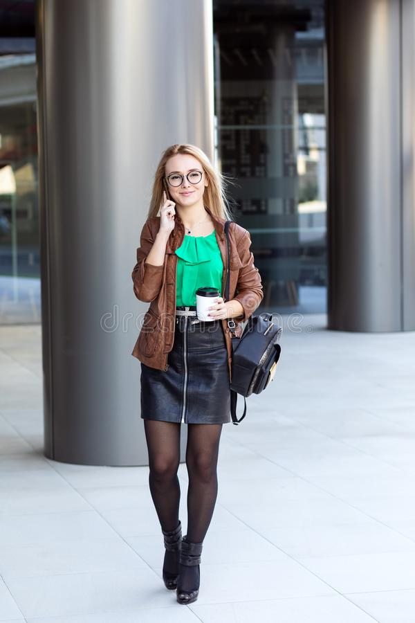 Femme élégante avec les verres élégants buvant du café et ayant une conversation téléphonique en dehors de l'immeuble de bureaux  photographie stock
