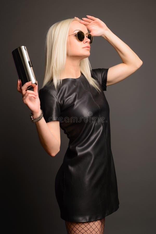 Femme élégante d'élégance dans la robe en cuir noire avec le petits sac et montre argentés photos stock
