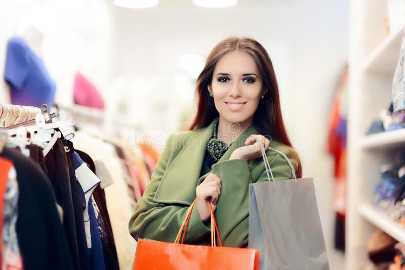 Femme élégante d'achats portant un manteau vert dans le magasin de mode image libre de droits
