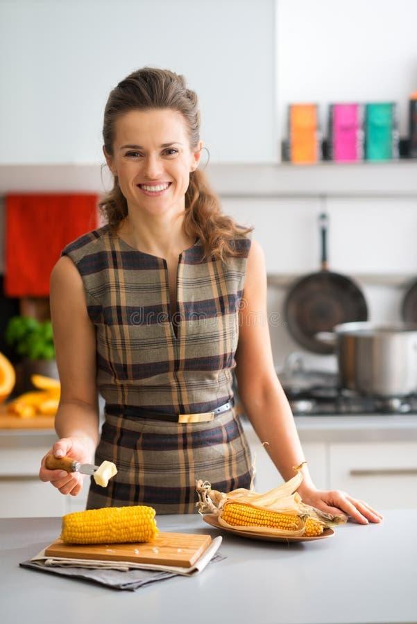 Femme élégante dans la cuisine tout en mettant le beurre sur l'épi de maïs photo libre de droits