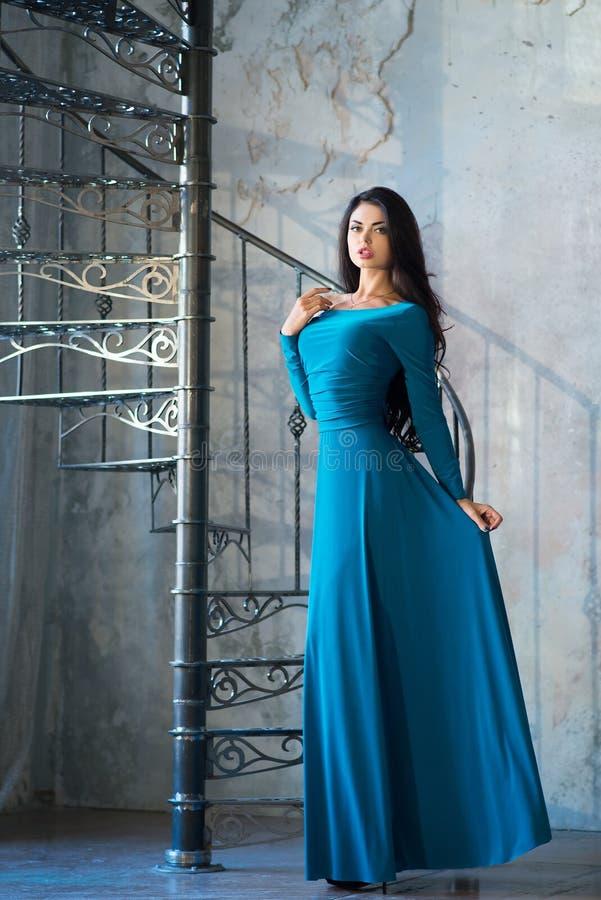Femme élégante dans la longue robe violette de luxe tenant les escaliers proches photo stock