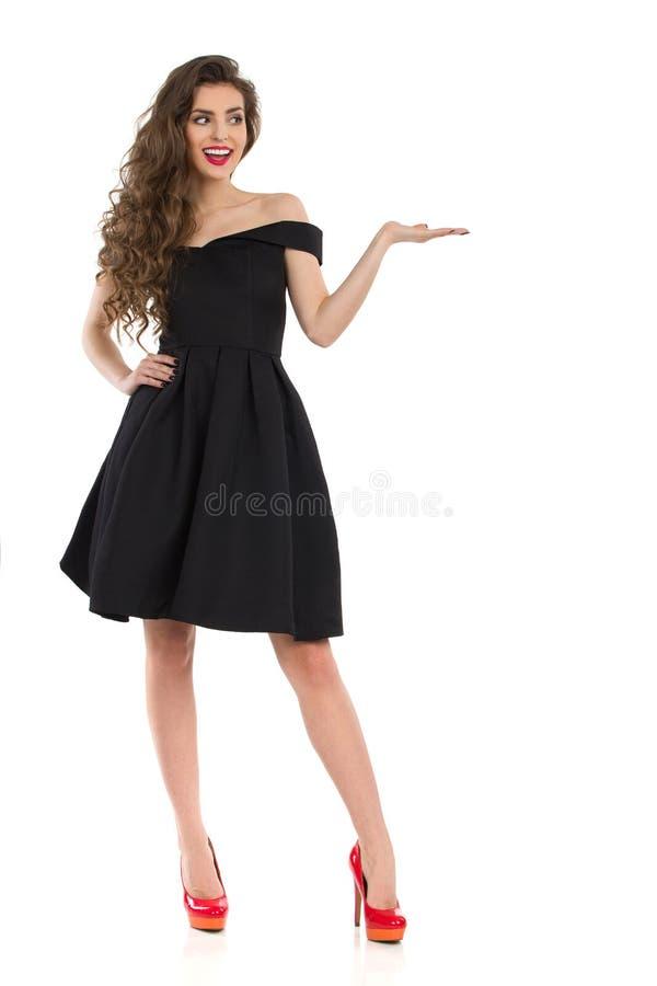 8f4b3d9b148 La belle jeune femme dans la robe de cocktail noire élégante et des talons  hauts rouges se tient avec la main augmentée