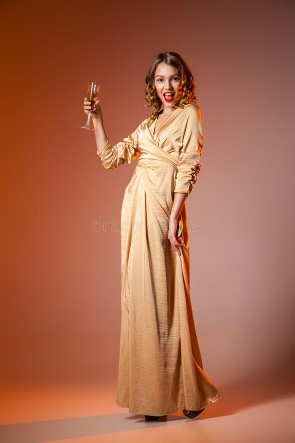 Femme élégante dans la robe d'or avec le verre à vin photo stock