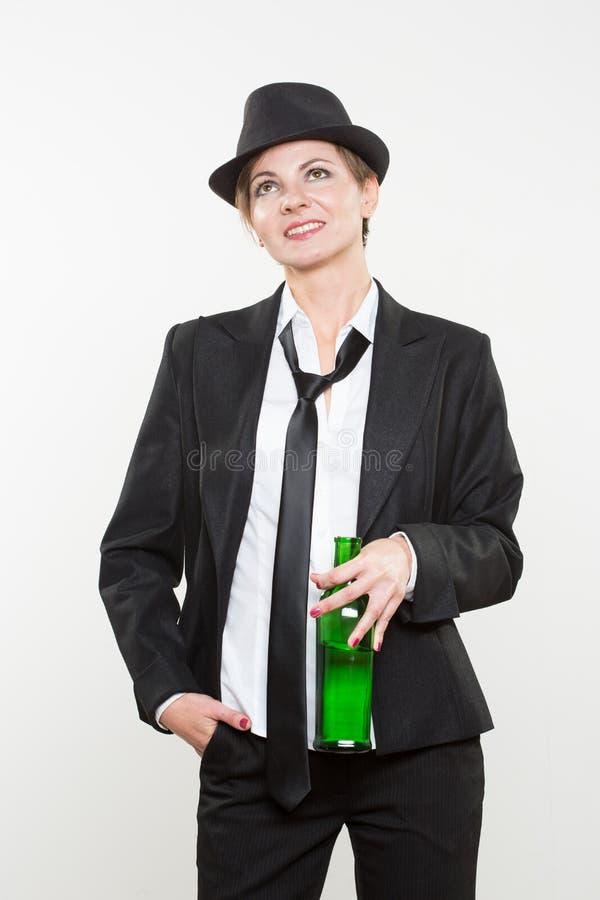 Femme élégante dans un costume, tenant la bouteille d'alcool images libres de droits