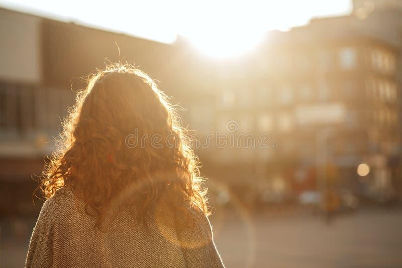 Femme élégante de brune avec les cheveux luxuriants se tenant à l'avenue et regardant en avant L'espace pour le texte photo libre de droits