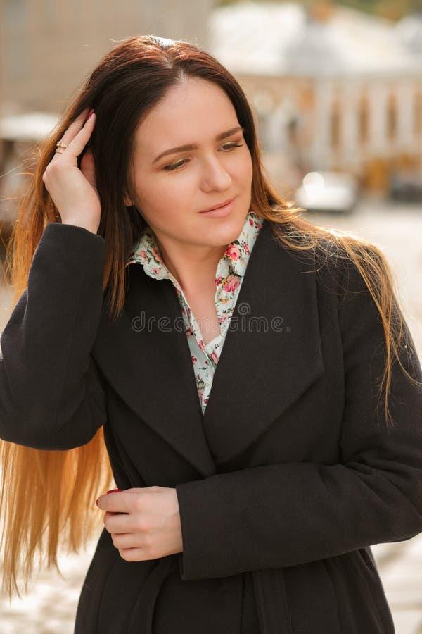 Femme élégante de brune avec de longs cheveux portant le manteau bleu à la mode a image stock