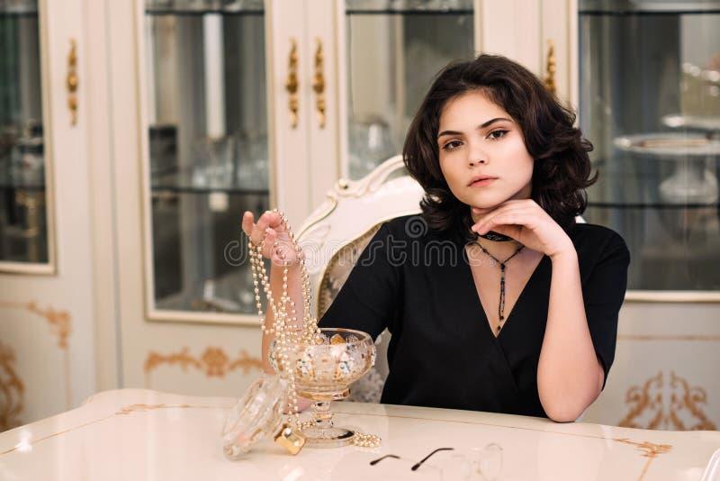 Femme élégante élégante de brune dans l'intérieur riche de beauté, robe noire de port photo stock