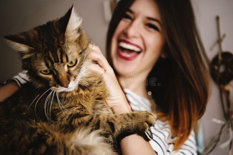 Femme élégante de hippie jouant avec son chat dans la chambre moderne photographie stock libre de droits