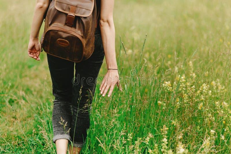 Femme élégante de hippie marchant dans l'herbe et tenant l'herbe disponible image libre de droits