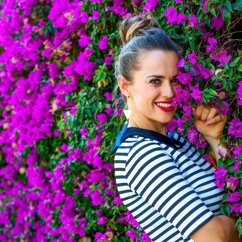 Femme élégante de sourire près de lit de fleurs magenta coloré photo stock