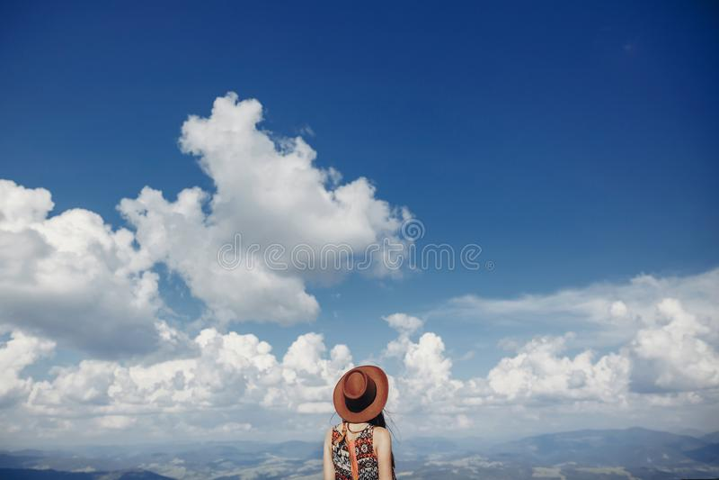Femme élégante de voyageur dans le chapeau regardant le ciel et les montagnes gratte-culs image libre de droits