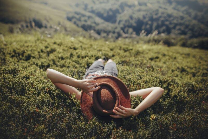 Femme élégante de voyageur dans le chapeau se trouvant sur l'herbe et détendant dans le MOU image stock
