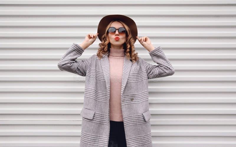 Femme élégante en manteau à carreaux, chapeau rond posé sur le mur blanc de la rue de la ville photographie stock