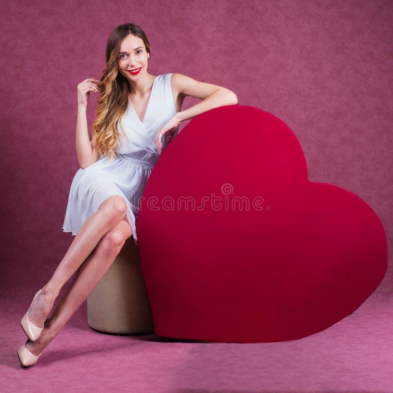 Femme élégante et de mode tenant le coeur photographie stock