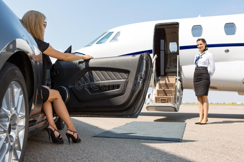 Femme élégante faisant un pas hors de la voiture sur le terminal images stock