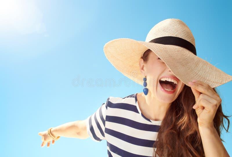 Femme élégante heureuse contre le ciel bleu se cachant derrière le chapeau de paille photo libre de droits
