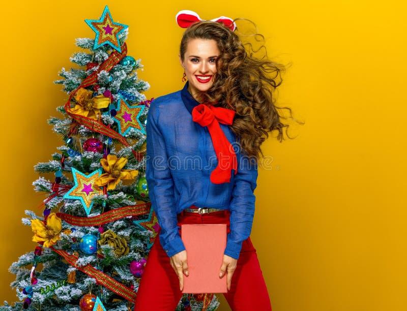 Femme élégante heureuse près d'arbre de Noël avec sauter de livre photographie stock libre de droits