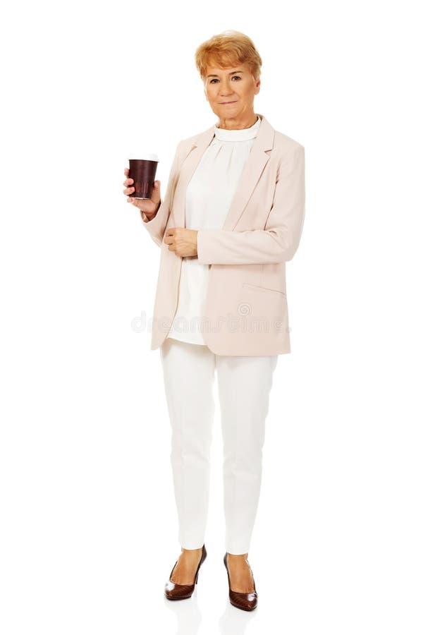 Femme élégante pluse âgé de sourire tenant la tasse de papier images libres de droits