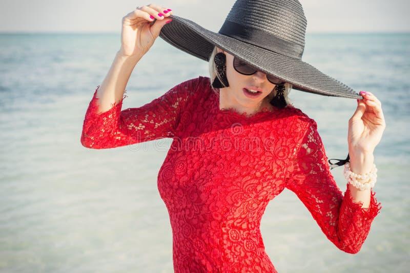 Femme élégante portant le chapeau noir d'été et la robe rouge sur la plage photographie stock libre de droits