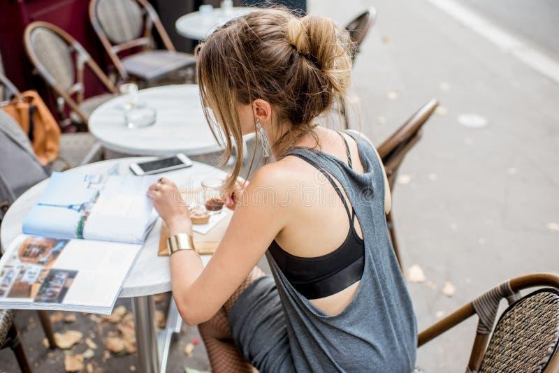 Femme élégante s'asseyant au café français image libre de droits