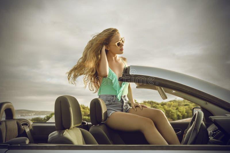 Femme élégante s'asseyant dans une voiture chique image libre de droits