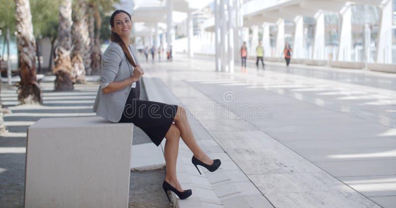 Femme élégante s'asseyant sur un banc sur une promenade photographie stock