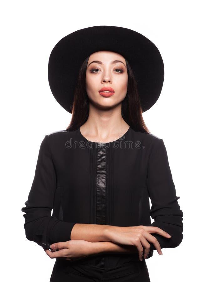 Femme élégante utilisant la robe noire et le chapeau noir image stock