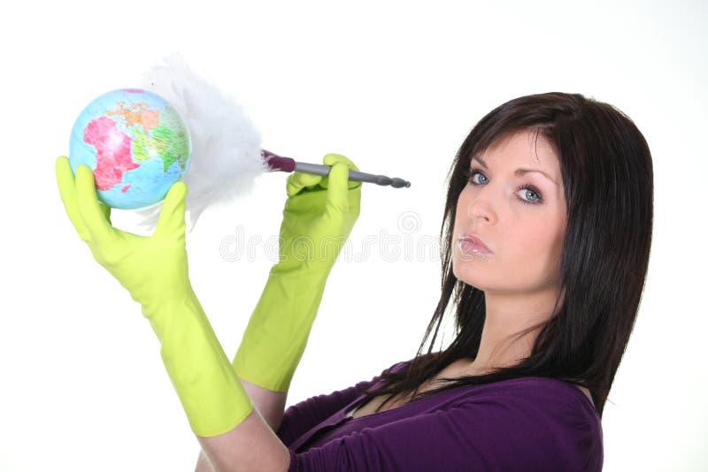 Femme époussetant un globe image stock