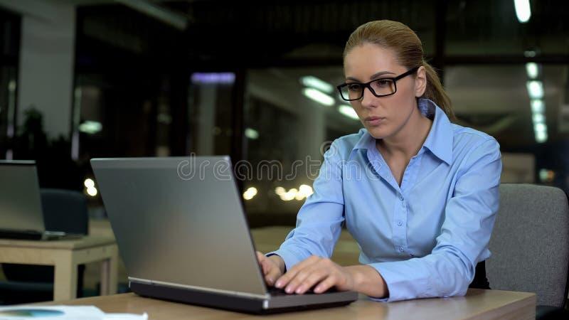 Femme épuisée d'affaires travaillant sur seul l'ordinateur portable dans le bureau la nuit, surcharge photographie stock libre de droits