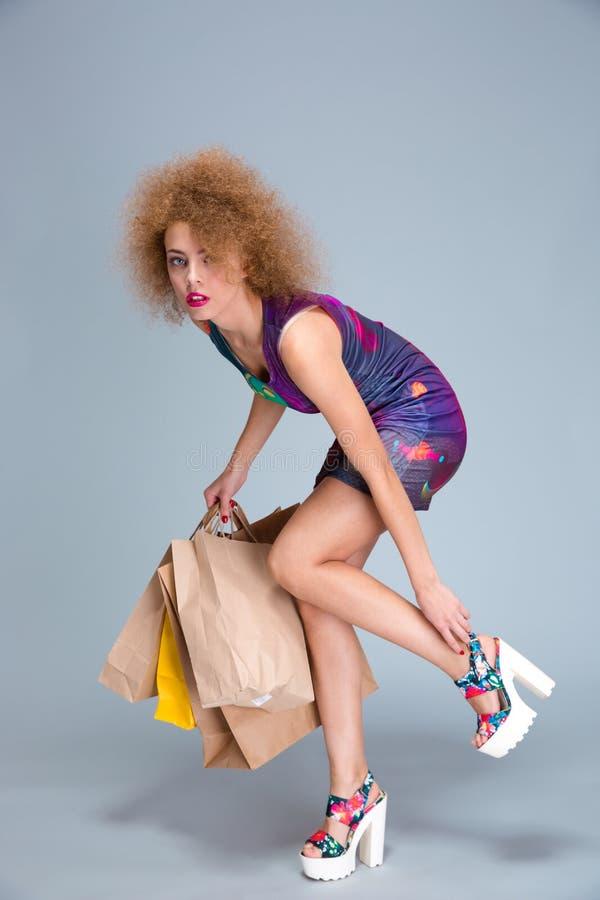 Femme épuisée la touchant blessant des jambes sur des achats photographie stock libre de droits