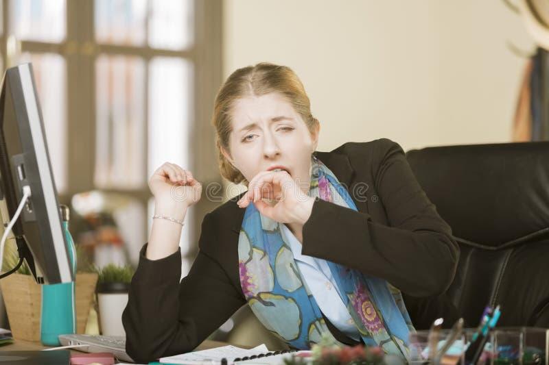 Femme épuisée ou ennuyée baîllant à son bureau photos stock