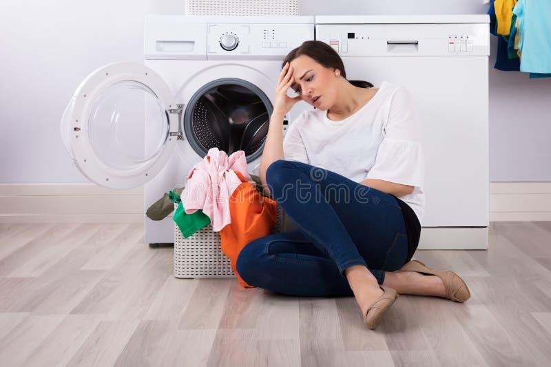 Femme épuisée s'asseyant avec le panier plein des vêtements image libre de droits