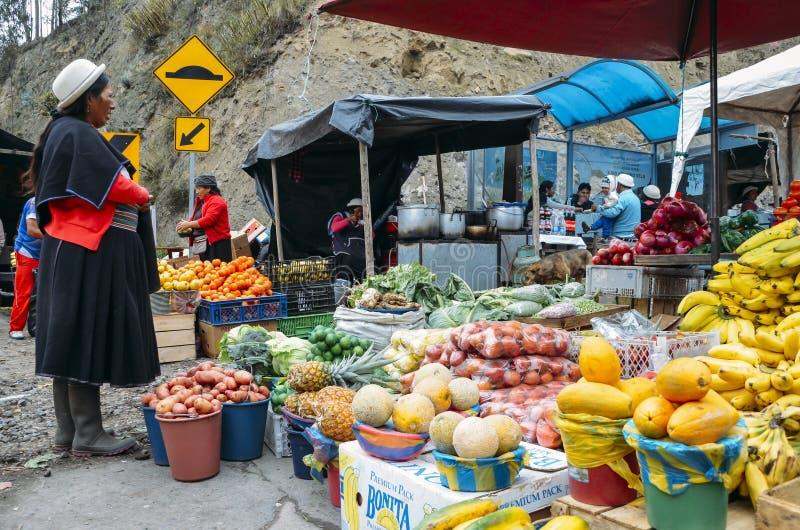 Femme équatorienne traditionnellement habillée inspectant les fruits tropicaux sur un marché image stock
