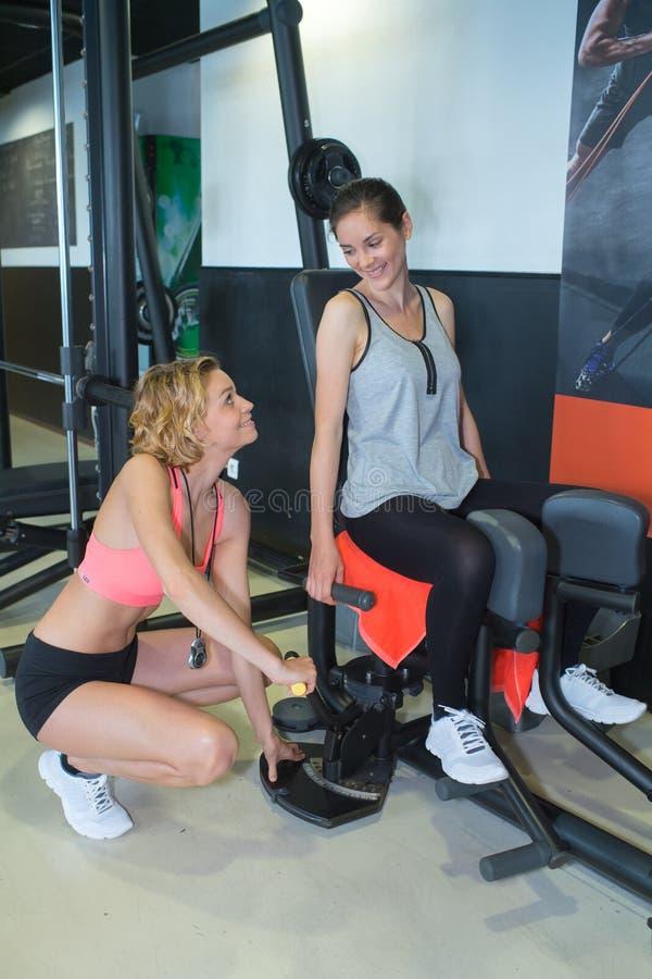 Femme établissant avec l'entraîneur personnel de forme physique dans le gymnase images libres de droits