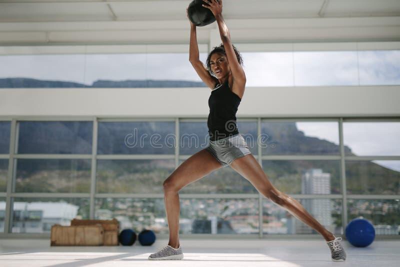Femme établissant avec la boule de forme physique photos libres de droits