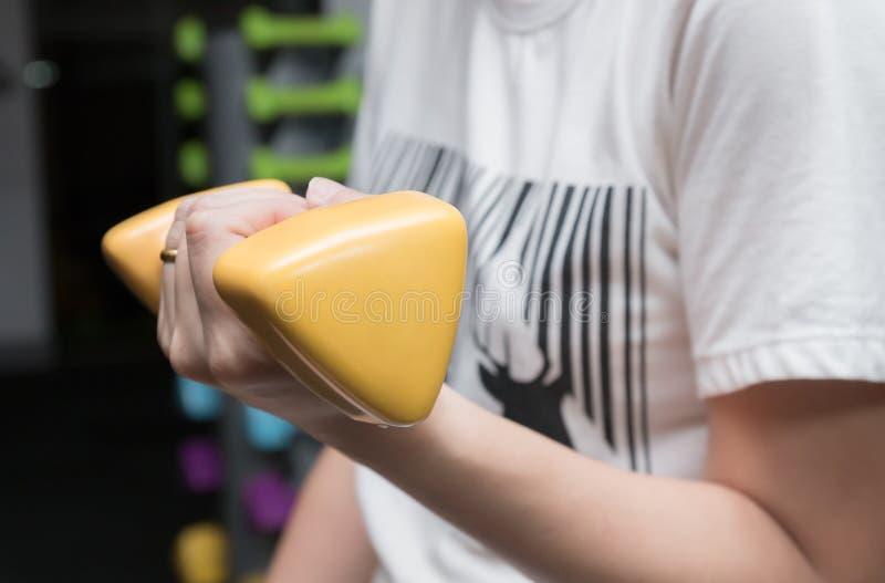 Femme établissant avec tenir l'haltère jaune de barbell au gymnase de forme physique photos stock