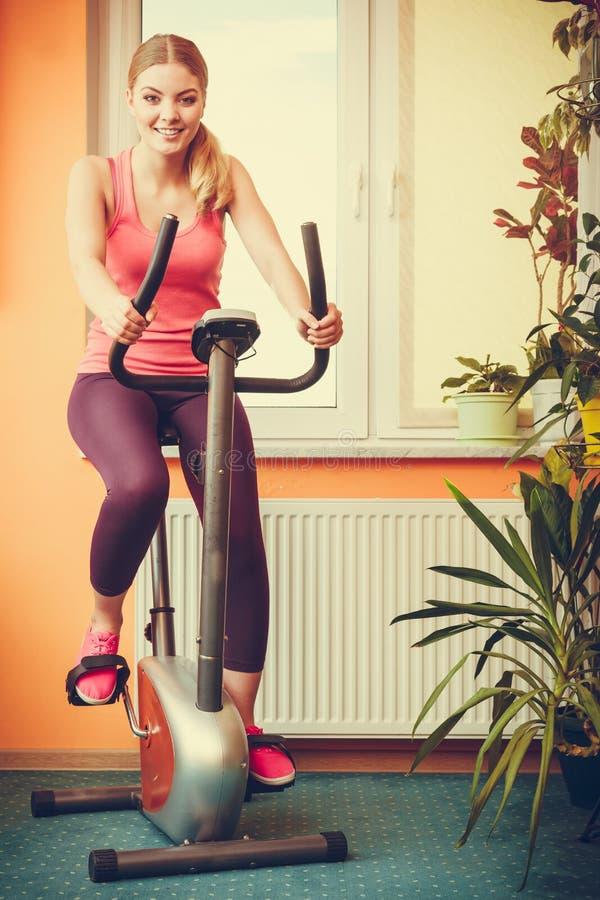 Femme établissant sur le vélo d'exercice Forme physique image libre de droits