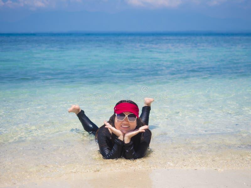 Femme étant heureuse sur l'eau claire images stock