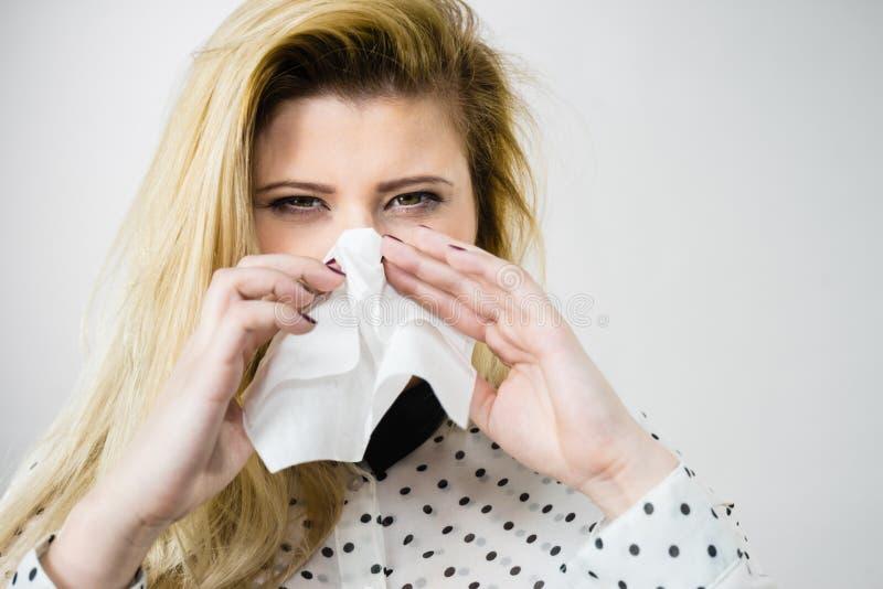Femme étant malade ayant l'éternuement de grippe dans le tissu photographie stock