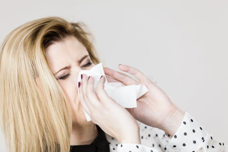 Femme étant malade ayant l'éternuement de grippe dans le tissu images stock