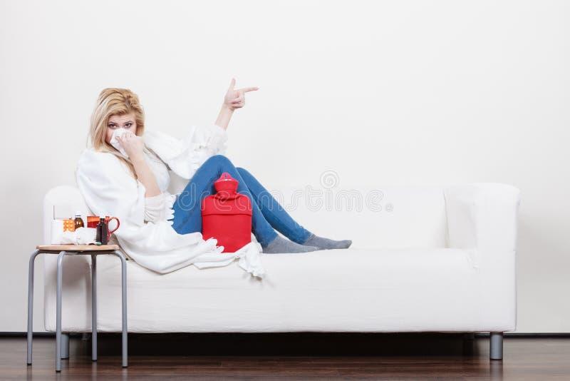 Femme étant malade ayant la grippe se trouvant sur le sofa photographie stock libre de droits