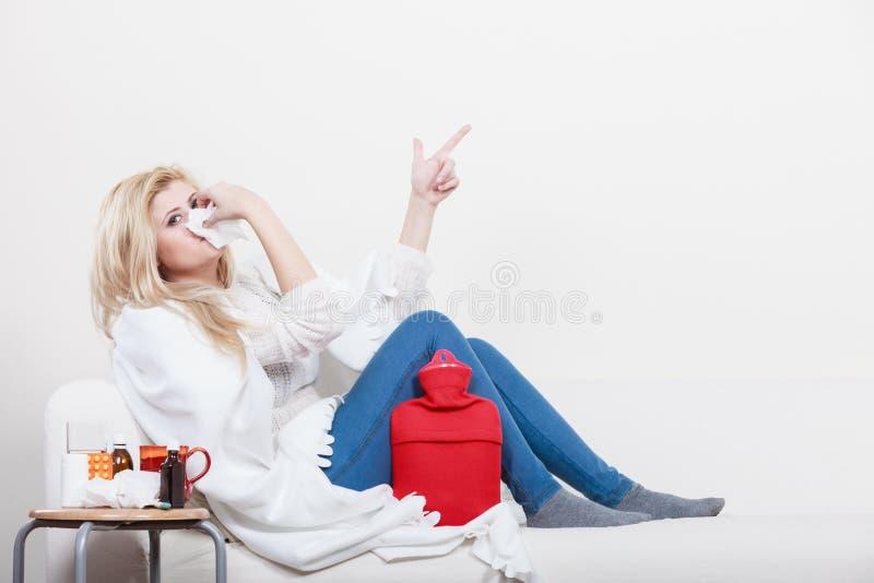 Femme étant malade ayant la grippe se trouvant sur le sofa photo stock