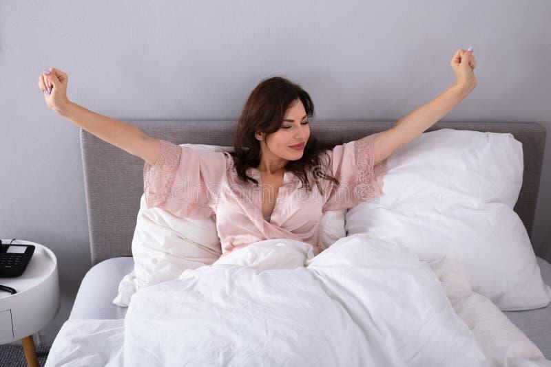Femme ?tirant ses bras sur le lit image libre de droits