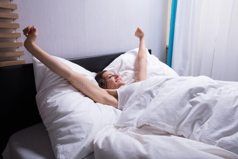 Femme étirant ses mains sur le lit photo libre de droits