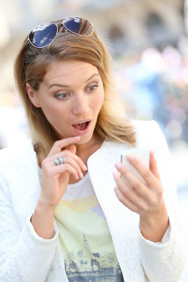 Femme étonné par des sms au téléphone images stock