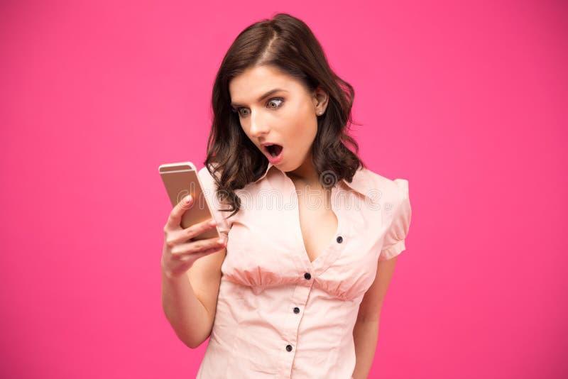 Femme étonnée à l'aide du smartphone images libres de droits