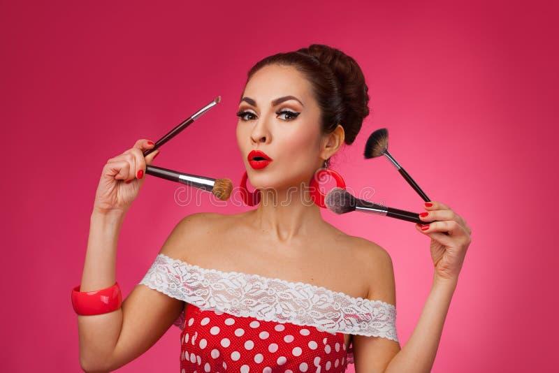 Femme étonnée avec des brosses de maquillage Elle est images stock