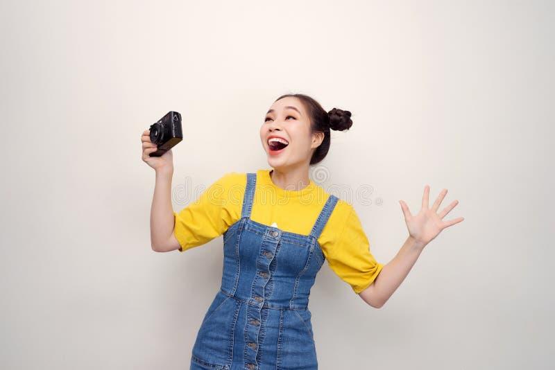 Femme étonnée, avec la coiffure supérieure de noeud, portant sur la salopette de denim, tenant la rétro caméra, sur le fond blanc photographie stock libre de droits