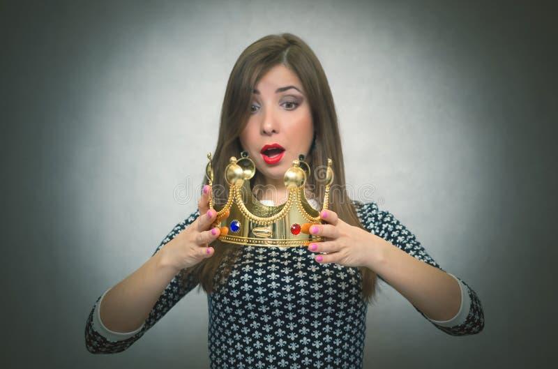 Femme étonnée avec la couronne d'or Premier concept d'endroit photographie stock libre de droits
